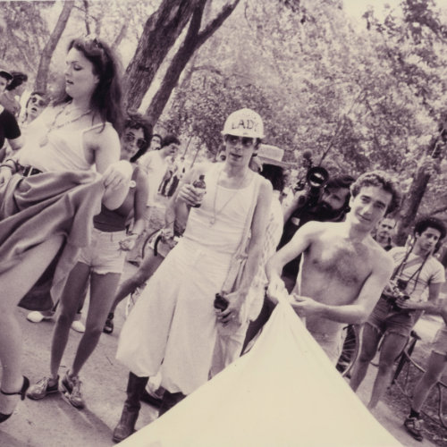 Photo of people gathered at Parc La Fontaine for one of the first gay marches in Montreal. It shows organiser John Banks in a construction hat reading ''Boss Lady.'' 1979. Crédit photo : Denis Plain. Fonds Denis Plain AGQ-F0142. Collection des Archives gaies du Québec.